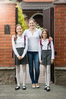 Junge mutter steht in der tür mit zwei töchtern, die zur schule gehen