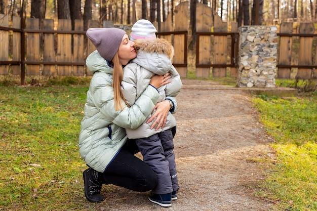 Junge mutter umarmt und beruhigt eine weinende tochter in einem herbstpark. elternschaftskonzept.