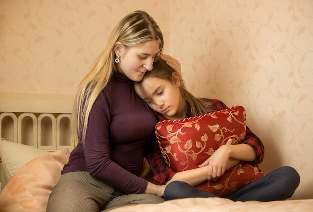 Junge mutter umarmt und tröstet tochter im teenageralter