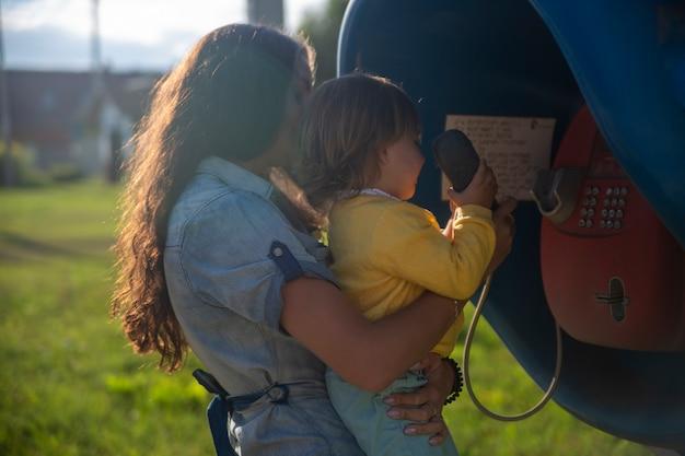 Junge mutter und baby rufen im sommer über ein festnetztelefon in der telefonzelle im dorf an. wandern mit der familie sonnigen sommertag bei sonnenschein. künstlerischer schwerpunkt