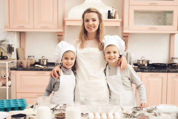 Junge mutter und glückliche kinder zusammen an der küche.
