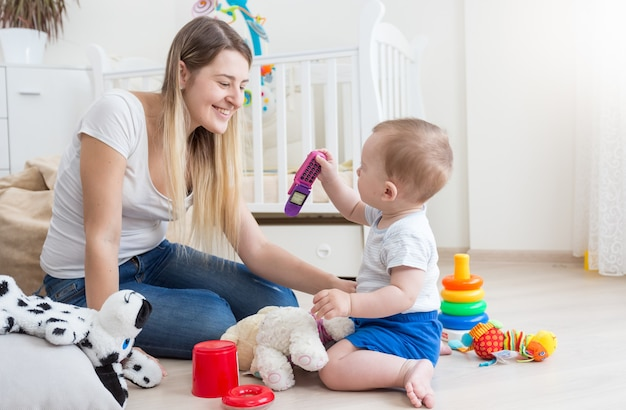 Junge mutter und ihr baby spielen mit dem handy