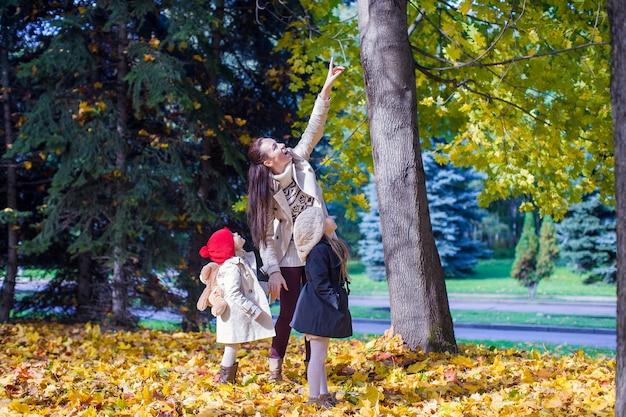 Junge mutter und ihre entzückende tochter, die reizend weg im gelben herbstwald an einem warmen sonnigen tag genießt