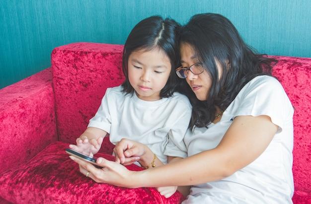 Junge mutter und ihre kleine tochter benutzen zu hause einen smartphone auf sofa