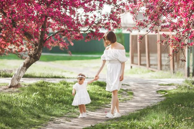 Junge mutter und ihre kleine tochter, die zusammen im frühjahr in die zeit des parks geht. glückliche familie im freien. lieben mit entzückendem baby.