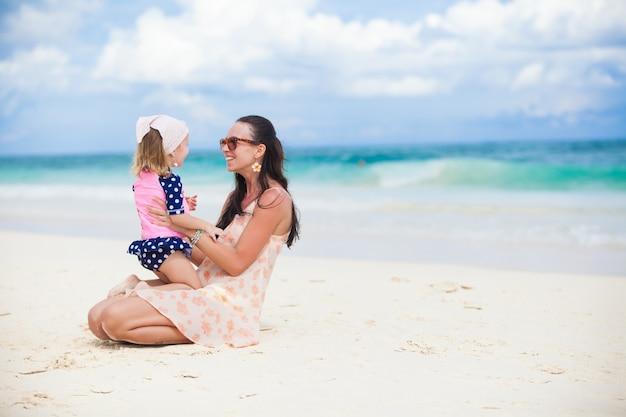 Junge mutter und ihre kleine tochter haben spaß am tropischen strand