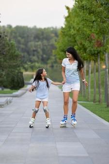Junge mutter und ihre kleine tochter rollerskaten im park