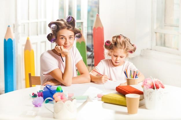 Junge mutter und ihre kleine tochter zeichnen zu hause mit bleistiften