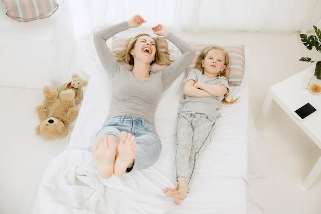 Junge mutter und ihre kleine tochter zu hause am sonnigen morgen. weiche pastellfarben. glückliche familienzeit am wochenende. muttertagskonzept. konzepte für familie, liebe, lebensstil, mutterschaft und zarte momente.