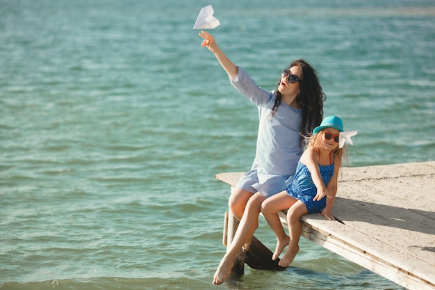 Junge mutter und ihre nette tochter an der seeseite, die papierflugzeuge in der luft und im lachen startet