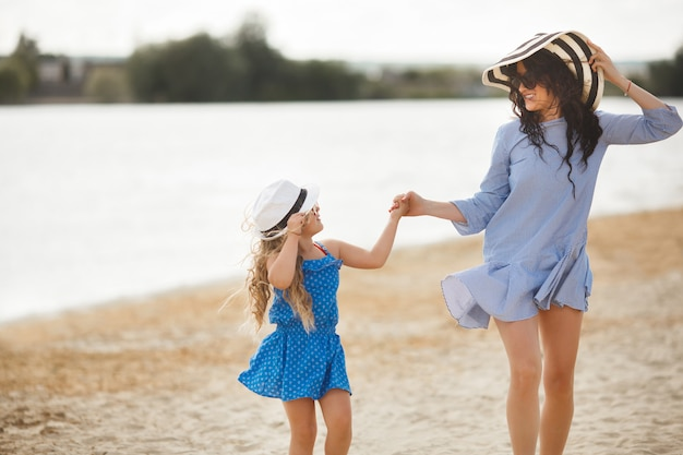 Junge mutter und ihre süße tochter am strand spaß haben. schöner familienurlaub. kleines fröhliches kind mit ihrer mutter am meer.