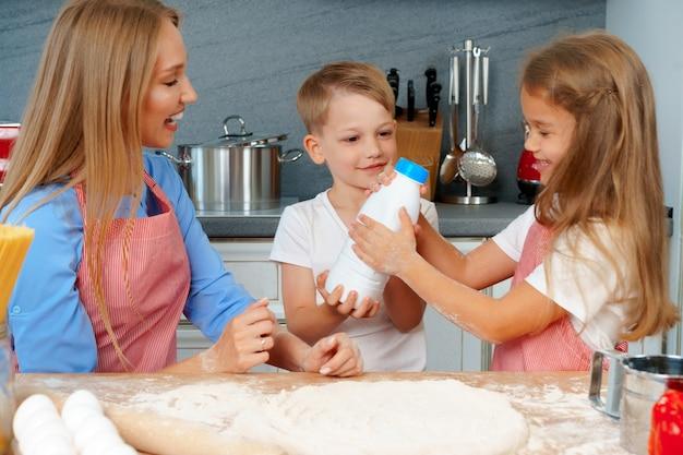 Junge mutter und ihre süßen kinder, die zusammen pizza kochen