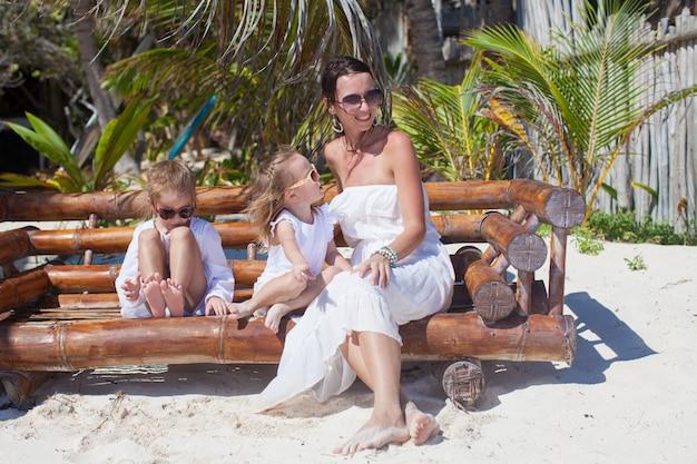 Junge mutter und ihre süßen töchter sitzen im strandkorb