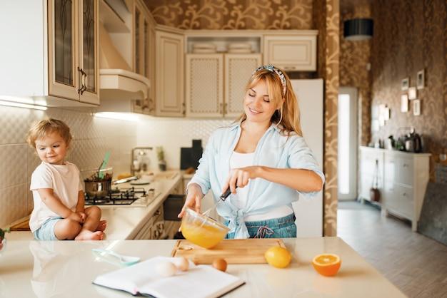 Junge mutter und ihre tochter mischen zutaten für kuchen in einer schüssel.