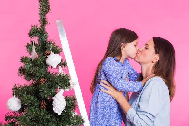Junge mutter und ihre tochter mit weihnachtsbaum auf rosa hintergrund