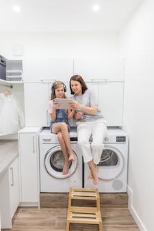 Junge mutter und ihre tochter spielen mit tablette in der waschküche, die auf waschmaschine sitzt
