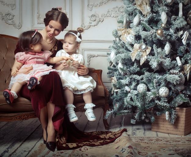 Junge mutter und ihre zwei kleinen töchter nähern sich weihnachtsbaum