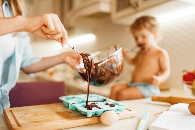 Junge mutter und kind bereiten gebäck zu und schmecken geschmolzene schokolade.