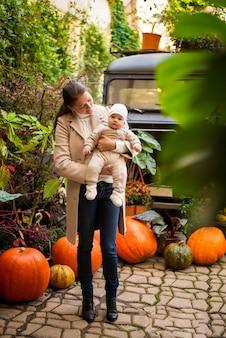 Junge mutter und kleine tochter auf kürbishintergrund, halloweenabend