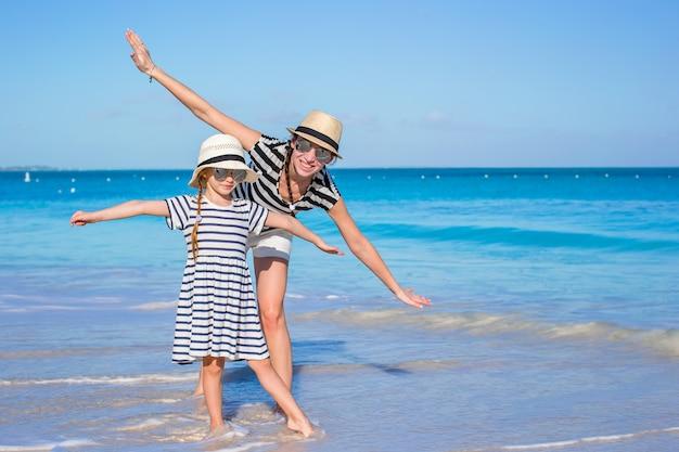 Junge mutter und kleine tochter haben spaß am tropischen strand