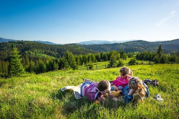 Junge mutter und kleine töchter liegen an einem mit gras bewachsenen hang oder bewundern die herrliche aussicht auf einen fuchs, der auf den hügeln wächst