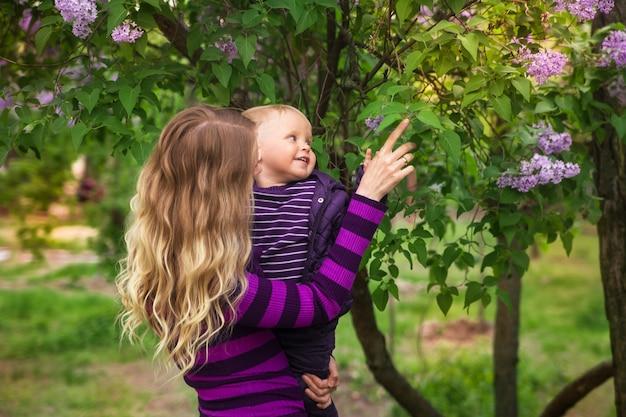 Junge mutter und kleiner sohn im blühenden lila frühlingsgarten am muttertag