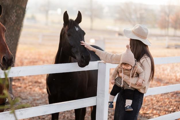 Junge mutter und kleines baby nahe einem pferd im sonnigen herbsttag