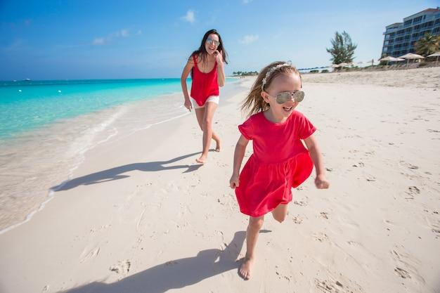 Junge mutter und kleines mädchen haben spaß am tropischen strand