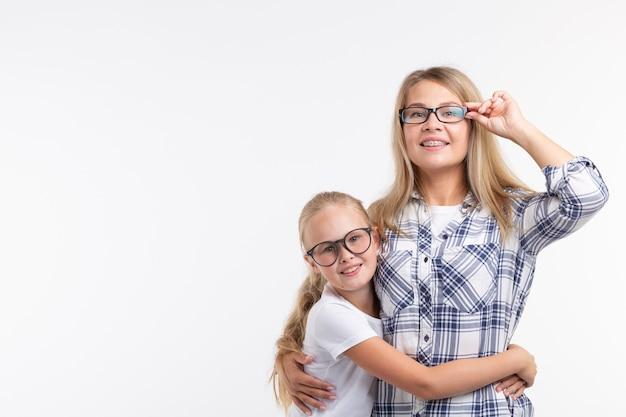Junge mutter und lachendes kind in modebrille haben spaß auf weißer wand
