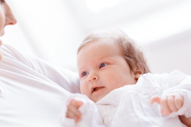 Junge mutter und neugeborenes baby im weißen schlafzimmer