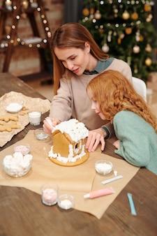 Junge mutter und niedliche kleine tochter, die hausgemachtes lebkuchenhaus mit schlagsahne verziert, während sie durch tisch gegen weihnachtsbaum stehen