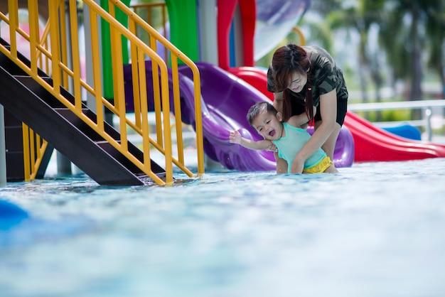 Junge mutter und sohn, die im pool mit glücklichem spielt