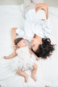 Junge mutter und süßes baby auf dem bett zu hause