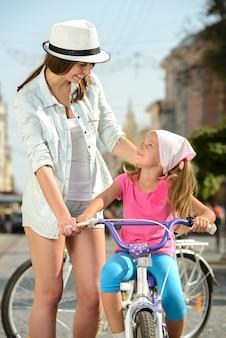 Junge mutter und tochter, die fahrrad auf die straße fährt.
