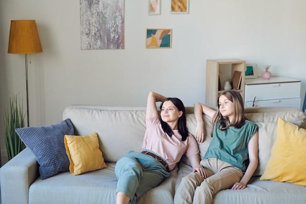 Junge mutter und tochter entspannen sich auf der couch im wohnzimmer gegen die wand mit hecheln, lampe, grüner hauspflanze und einigen möbeln