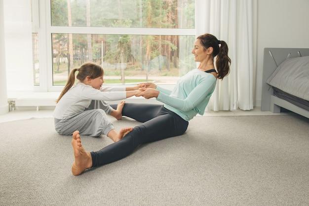 Junge mutter und tochter machen morgen yoga übung
