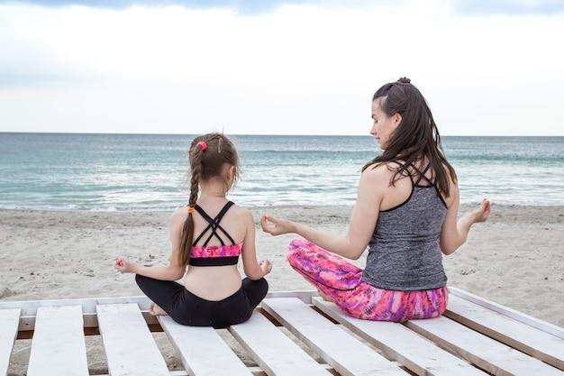 Junge mutter und tochter praktizieren yoga und meditation am meeresstrand.