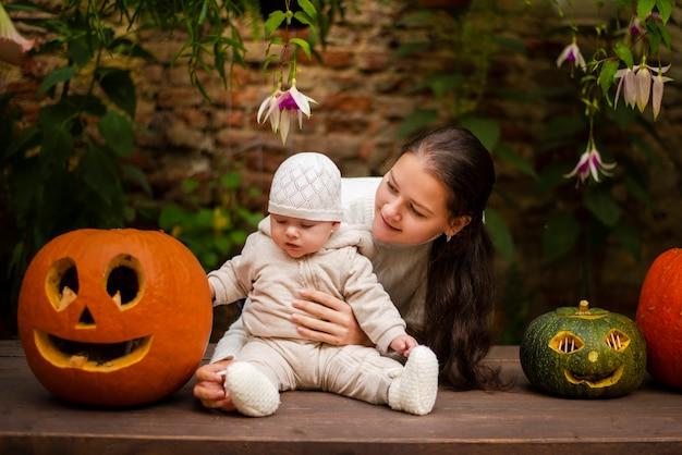 Junge mutter und tochter sitzen nahe kürbissen, halloweenabend