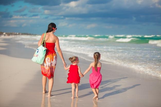 Junge mutter und zwei ihre modekinder am exotischen strand am sonnigen tag