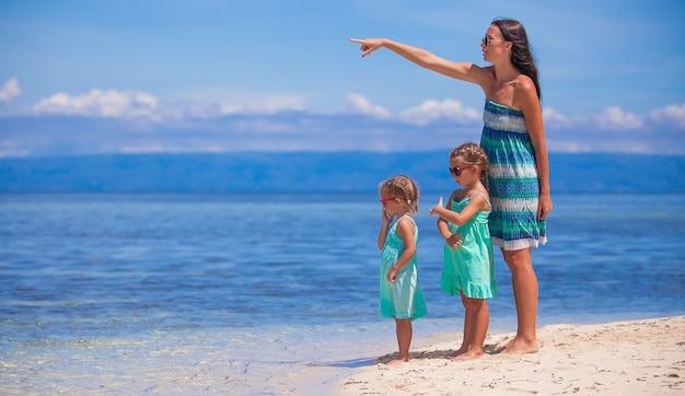 Junge mutter und zwei ihre töchter am exotischen strand am sonnigen tag