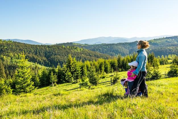 Junge mutter und zwei kleine töchter reisende stehen an einem hang mit einem herrlichen blick auf die mit dichtem tannenwald bedeckten hügel gegen den blauen himmel