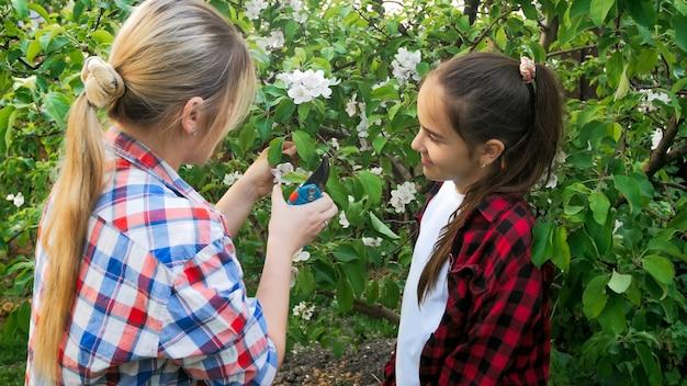 Junge mutter unterrichtet teenager-mädchen beim schneiden von ästen und kümmert sich um den garten.