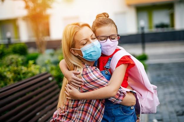 Junge mutter verabschiedet sich auf einem schulhof von ihrer kleinen tochter mit gesichtsschutzmaske. sie tragen gesichtsschutzmasken. zurück zum schulkonzept.