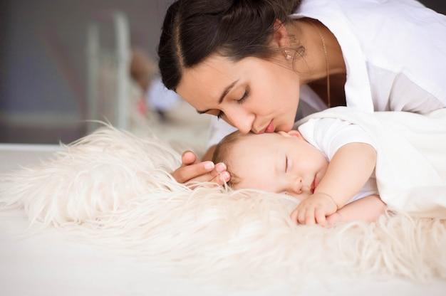Junge mutter, zärtlich ihr neugeborenes baby halten