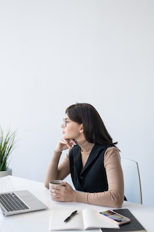 Junge nachdenkliche analystin mit getränk, die überlegt, wie man mit der finanziellen situation des unternehmens vor dem laptop umgeht