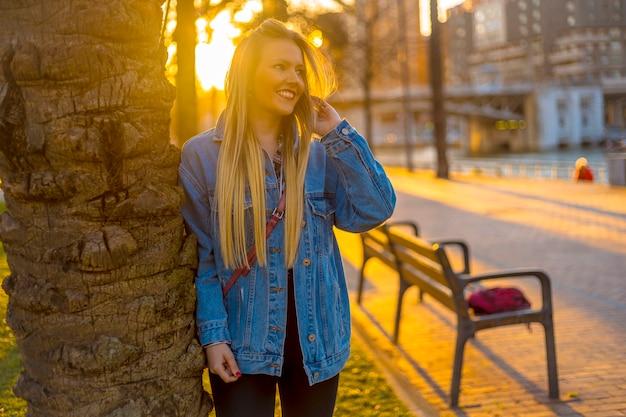 Junge nachdenkliche blondine in einem baum mit einer cowgirljacke auf einem sonnenuntergang