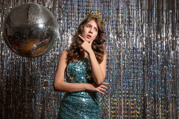 Junge nachdenkliche schöne dame, die blaugrünes glänzendes kleid mit pailletten mit krone in der partei trägt
