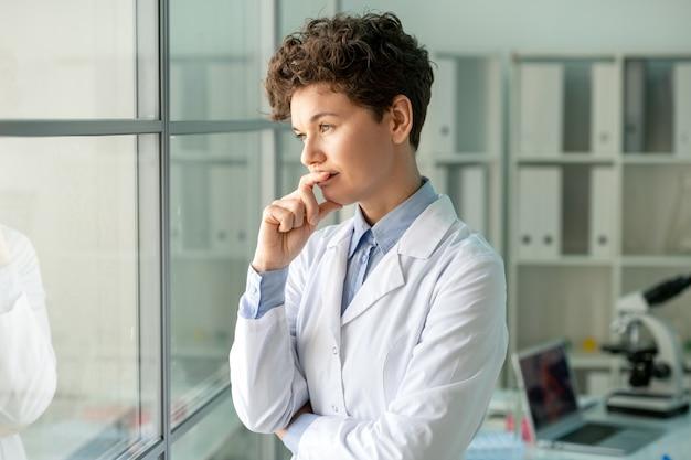 Junge nachdenkliche wissenschaftlerin oder laborarbeiterin im weißmantel, die durch glaswand gegen ihren arbeitsplatz mit laptop und mikroskop steht