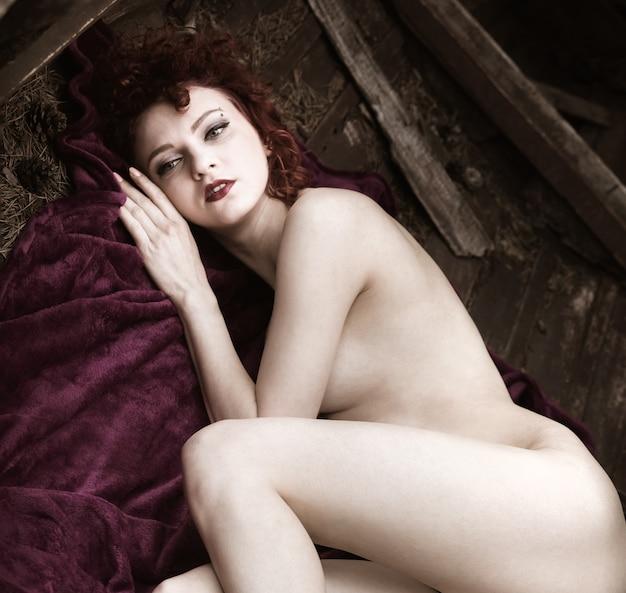 Junge nackte frau. schönheits- und nacktheitskonzept. junge völlig nackte rothaarige frau posiert im freien in einem alten holzboot