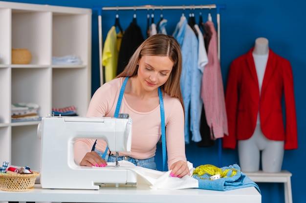 Junge näherin, die an ihrer nähmaschine auf textilfabrik arbeitet